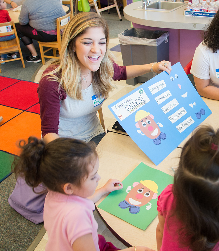 Female student teacher reads classroom rules to children seated at table